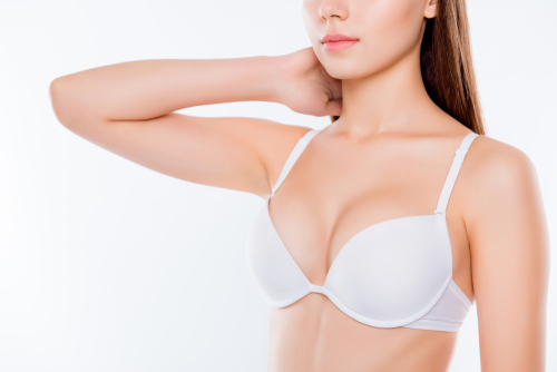 Cropped close up photo of beautiful womans breast clothed in white classic bra cups she is touching neck skinny slender slim body flawless skin-img-blog