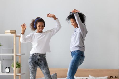 Slim mom dancing with daughter