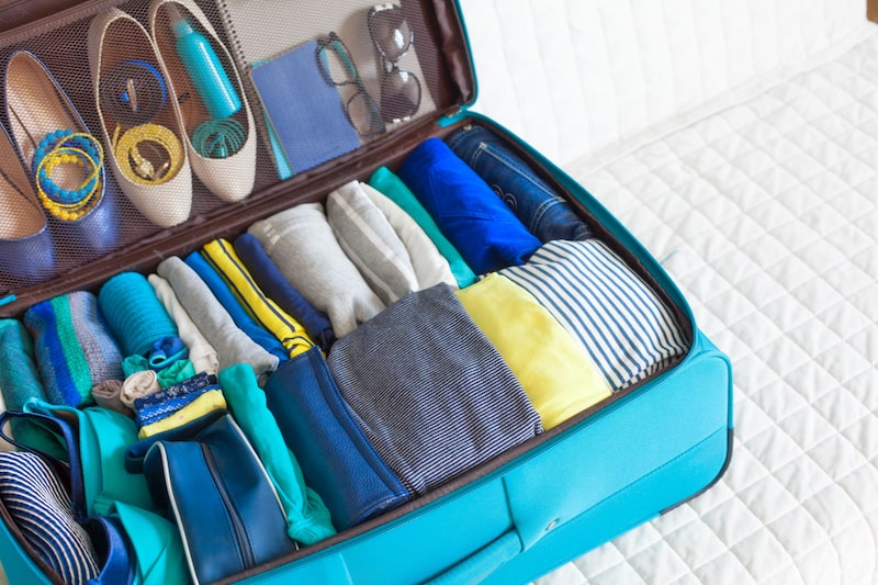 Full suitcase holding blue and yellow clothes.