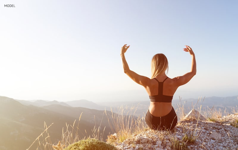 Women sitting on a cliff with her arms lifted, showing her back.
