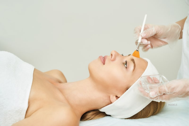 Woman getting a chemical peel with her aesthetician brushing solution on her forehead.