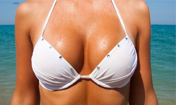 Close-up woman's breasts in a white bikini.